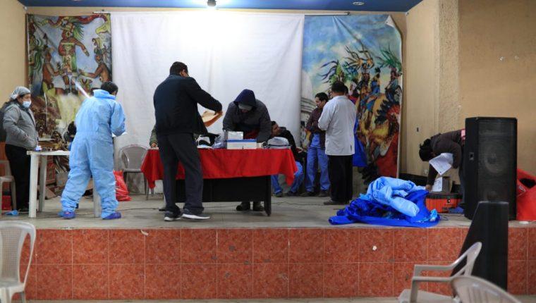 Personal del Instituto Nacional de Ciencias Forenses en el salón comunal de Nahualá. (Foto Prensa Libre: Carlos Hernández)