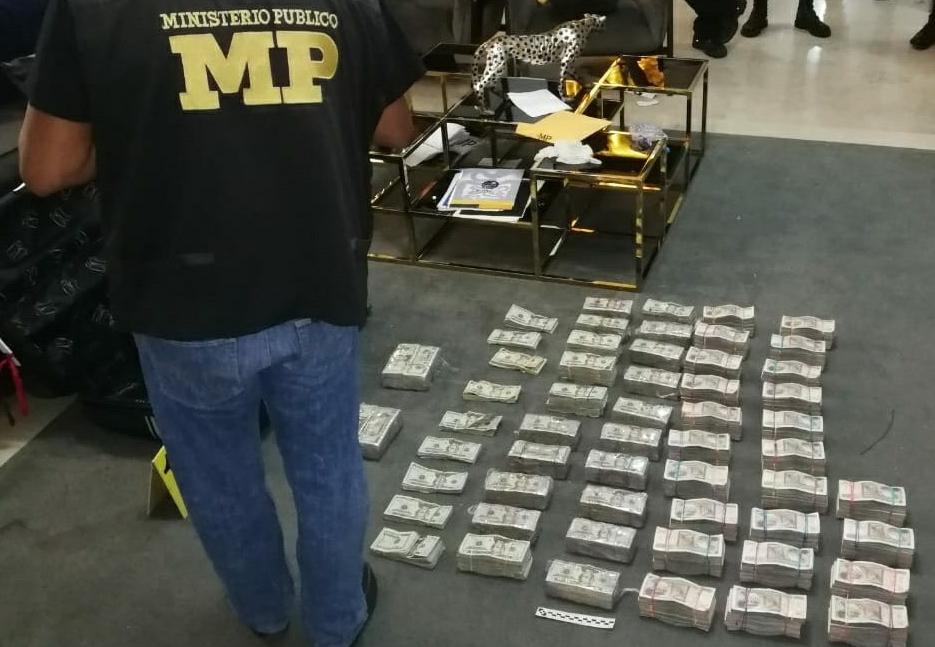 Un fiscal del MP contabiliza  una gran cantidad de dólares hallados en uno de los inmuebles cateados el miércoles. (Foto: MP)