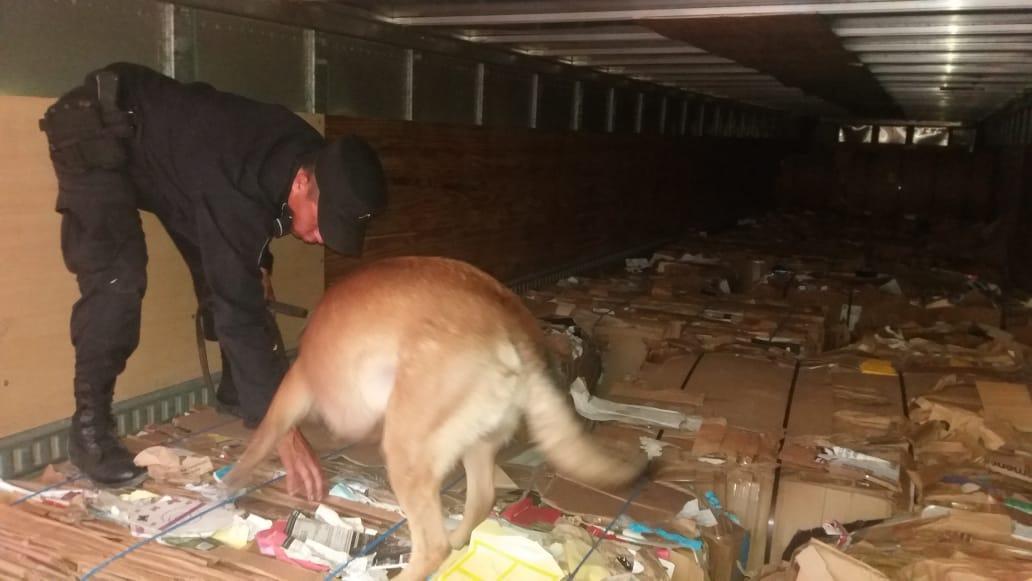 Un agente revisa el cargamento de droga que iba dentro de un vehículo. El perro Andy alertó sobre el ilícito. (Foto. PNC El Salvador)