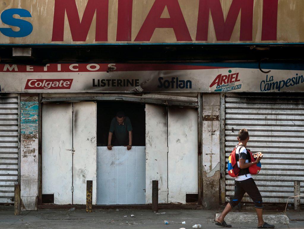 Un transeúnte mira una tienda cerrada, quemada durante el apagón que paralizó a Venezuela durante seis días.