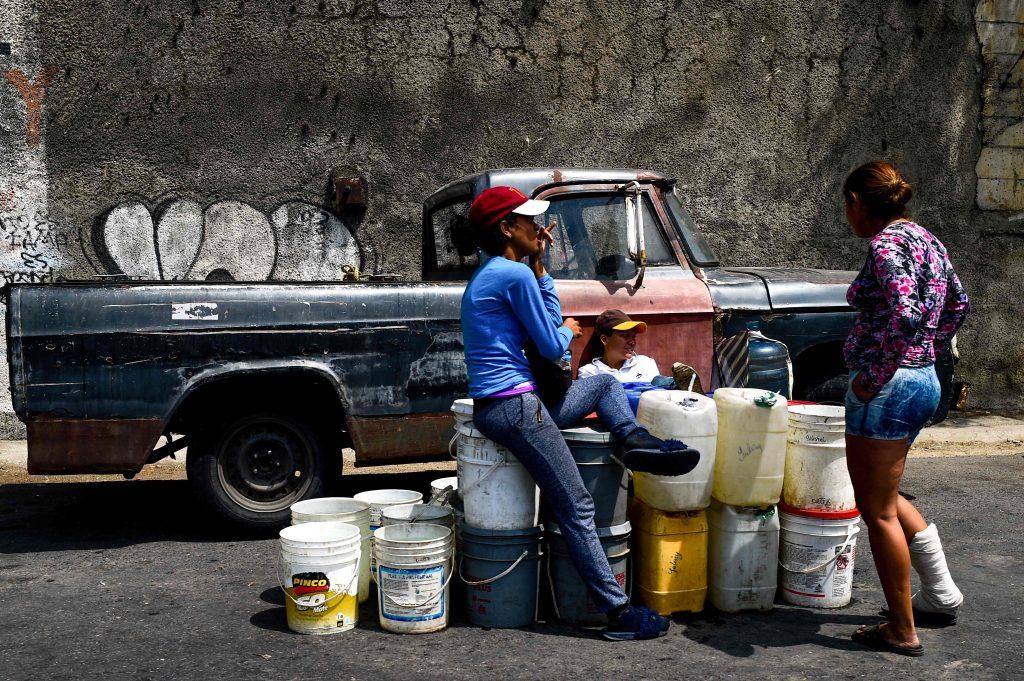 """La gente espera con los recipientes para recoger el agua que fluye desde la montaña Wuaraira Repano, también llamada """"El Ávila"""", en Caracas"""