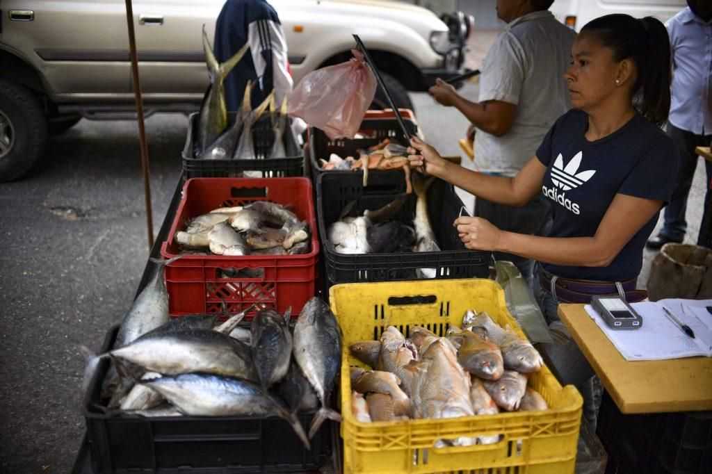 Una mujer vende pescado en un mercado callejero en Caracas, Venezuela, el 14 de marzo de 2019. Los empleados públicos de Venezuela fueron llamados a regresar al trabajo el jueves después de que el gobierno pusiera fin a una pausa de casi una semana causada por un apagón nacional sin precedentes que agudizó la ira generalizada contra Presidente Nicolás Maduro.