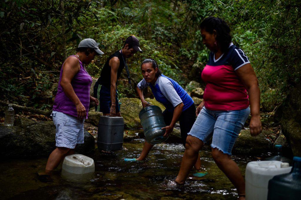 Venezolanos buscan agua en ríos y cualquier fuente en Caracas para poder llevar a sus casas.