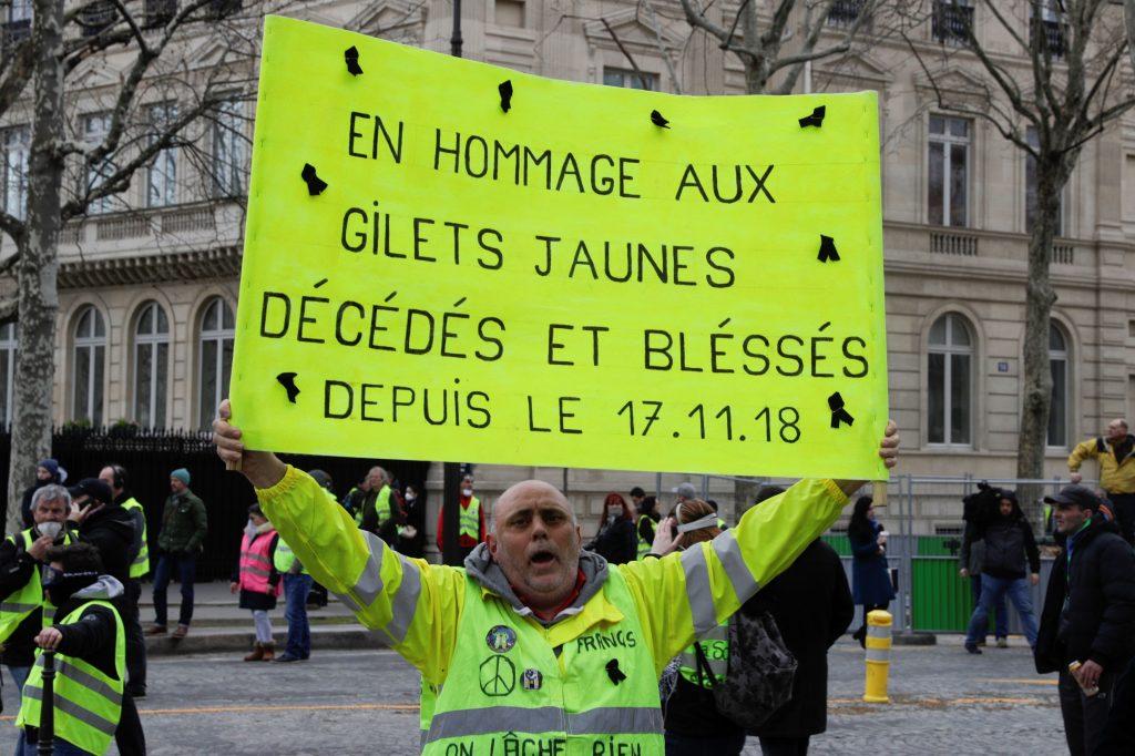"""Un manifestante de sostiene un cartel que dice """"En homenaje a los manifestantes de Yellow Vests que murieron y resultaron heridos desde el 17.11.18"""" en los Campos Elíseos de París el 16 de marzo de 2019. Foto Prensa Libre: AFP"""