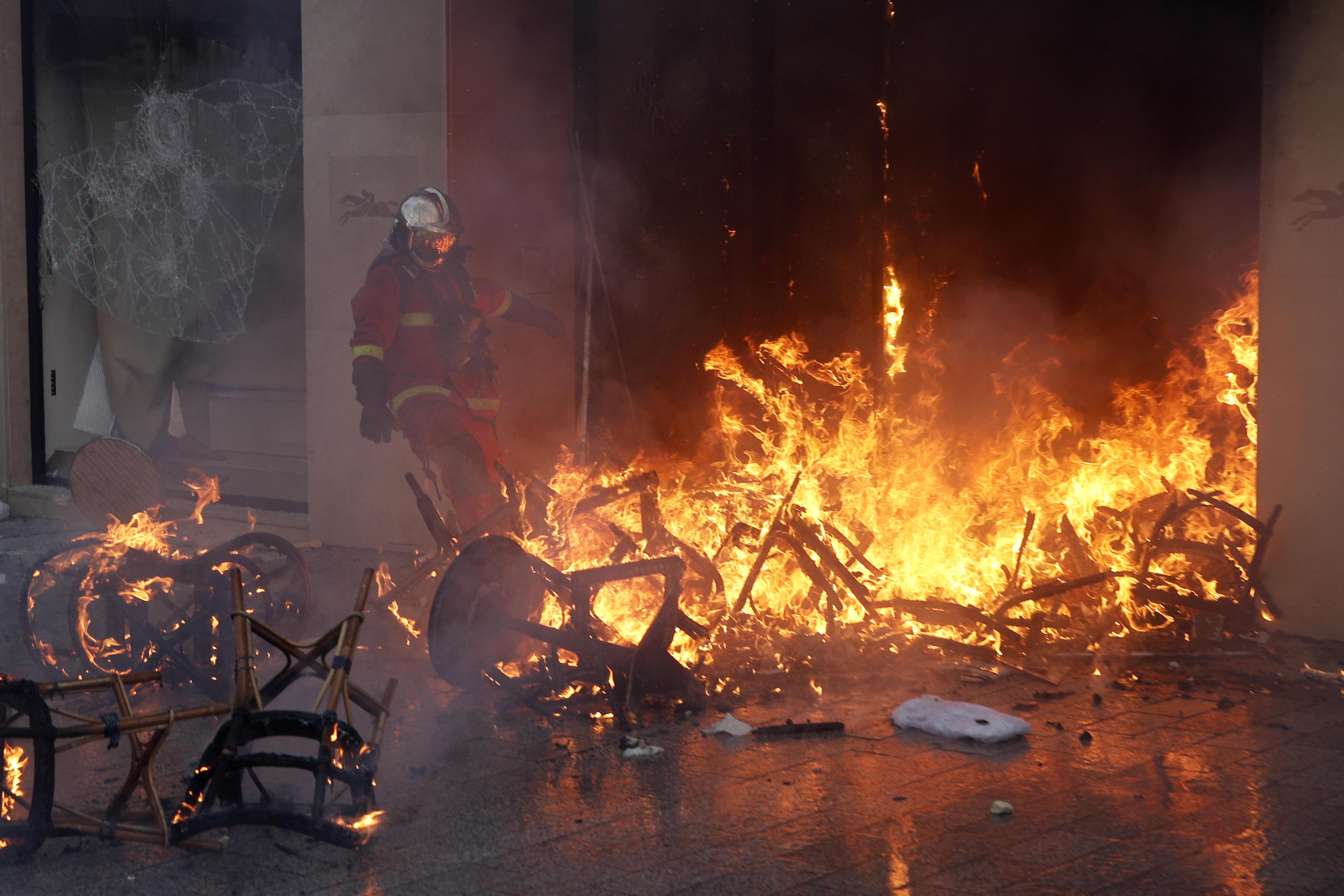 Un bomberos trata de apagar un incendio durante las protestas en los Campos Elíseos en Francia. Foto Prensa Libre: EFE