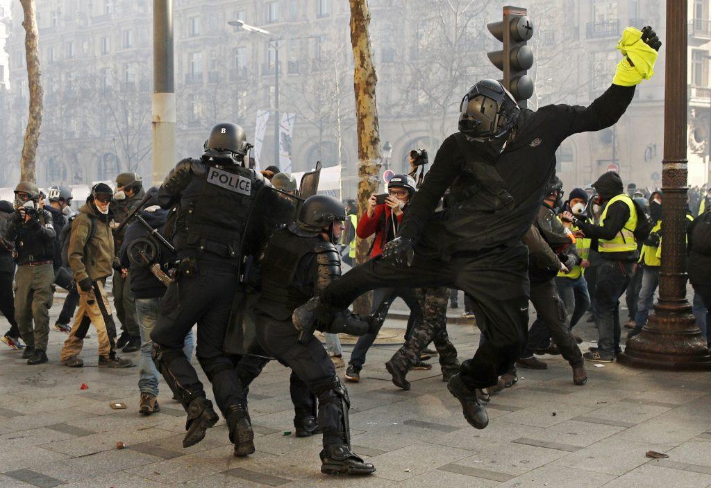 Un manifestante golpea a un policía durante las protestas de los Chalecos Amarillos en Francia. Foto Prensa Libre: EFE