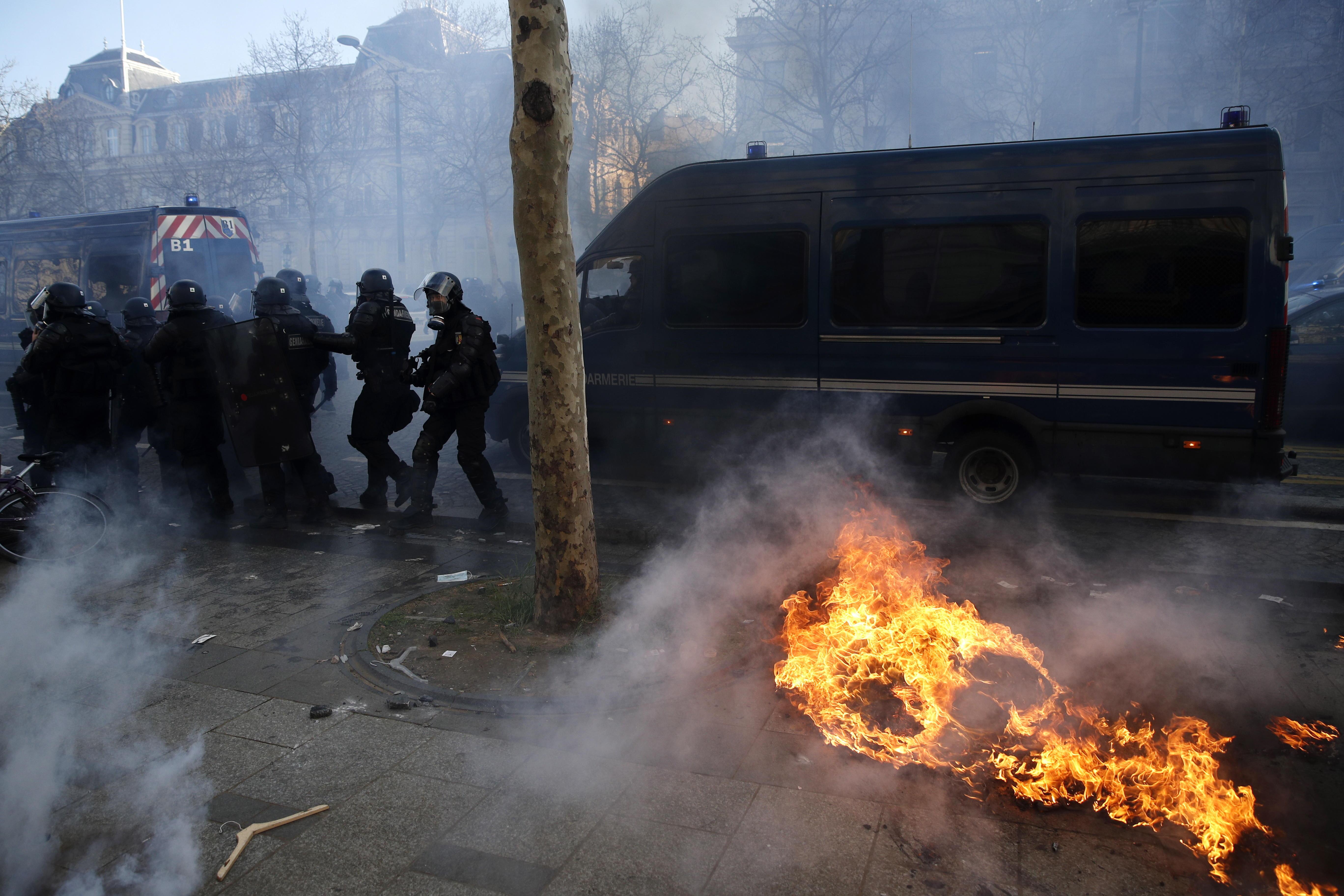 La policía antidisturbios corre en los Campos Elíseos cerca de un incendio durante la manifestación en Francia. Foto Prensa Libre: EFE