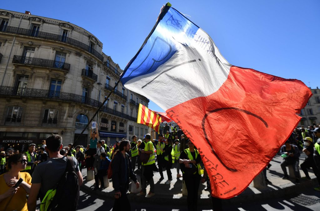 """Un manifestante ondea una bandera nacional francesa que lee """"RIC"""" (para el referéndum de ciudadanos iniciados) en Montpellier, sur de Francia. Foto Prensa Libre; AFP"""
