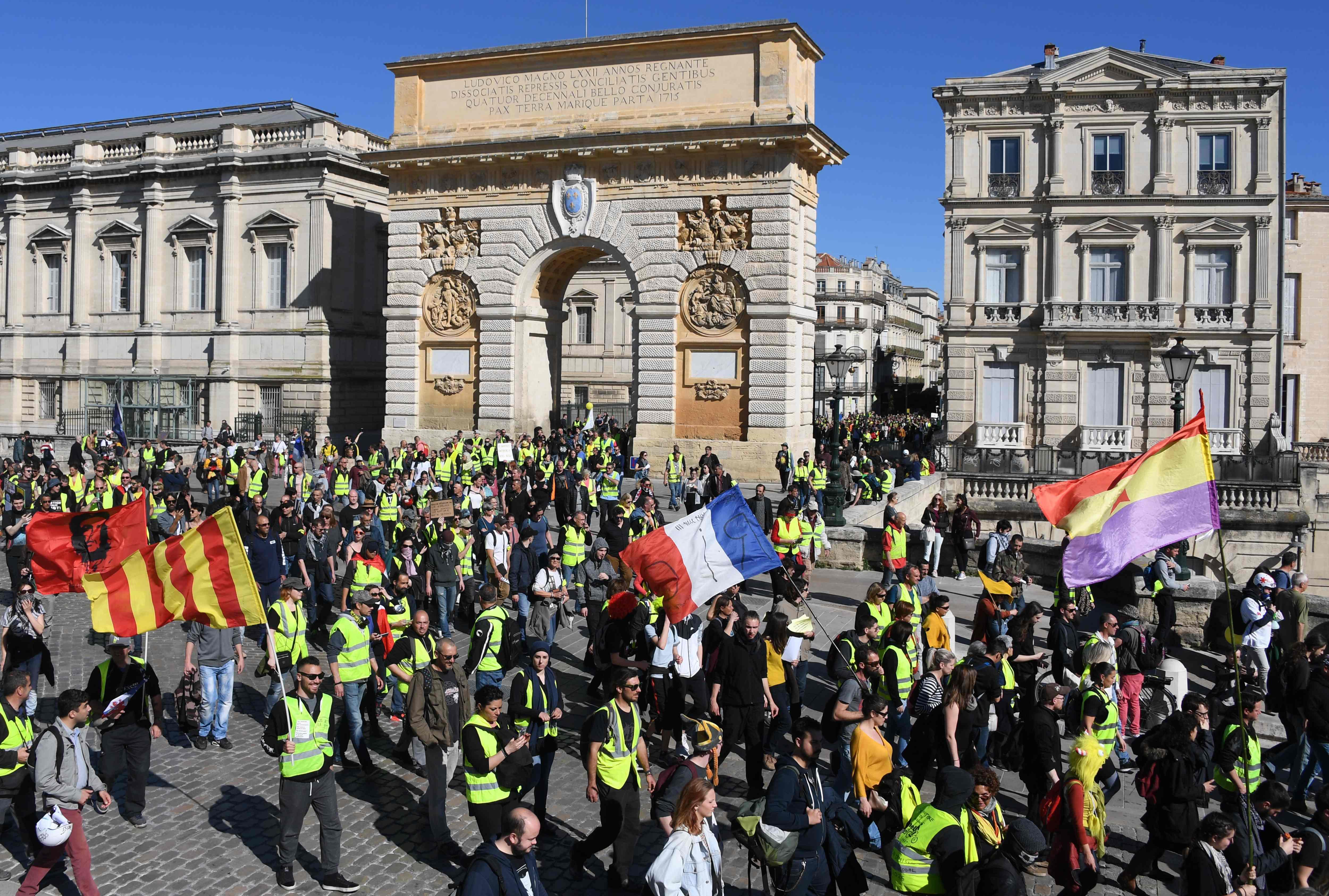 """Los manifestantes de """"chalecos amarillos"""" marchan frente a la Porte du Peyrou en Montpellier, en el sur de Francia. Foto Prensa Libre: AFP"""