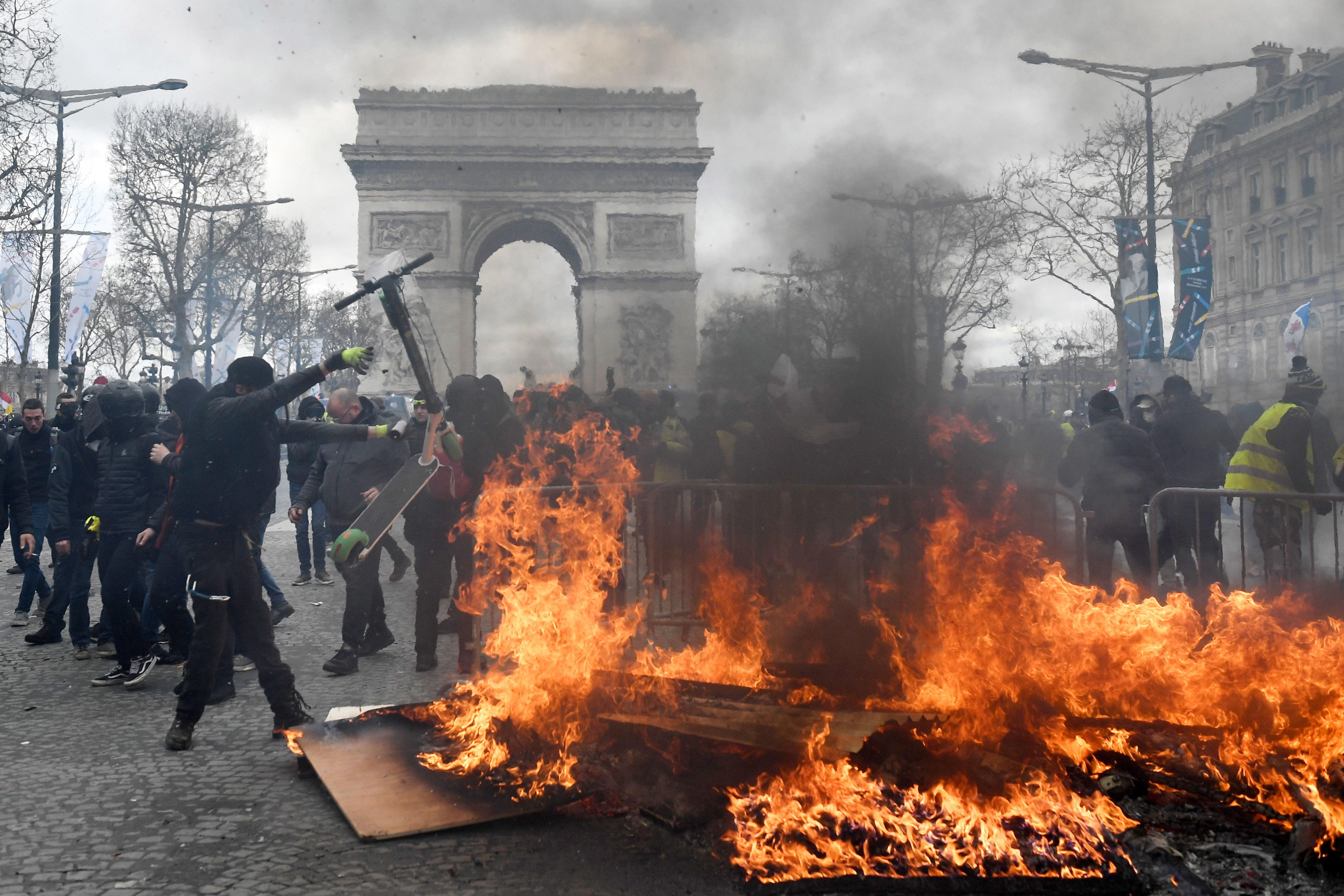Los manifestantes se enfrentan a las fuerzas policiales cuando estallan las protestas en los Campos Elíseos. Foto Prensa Libre: EFE