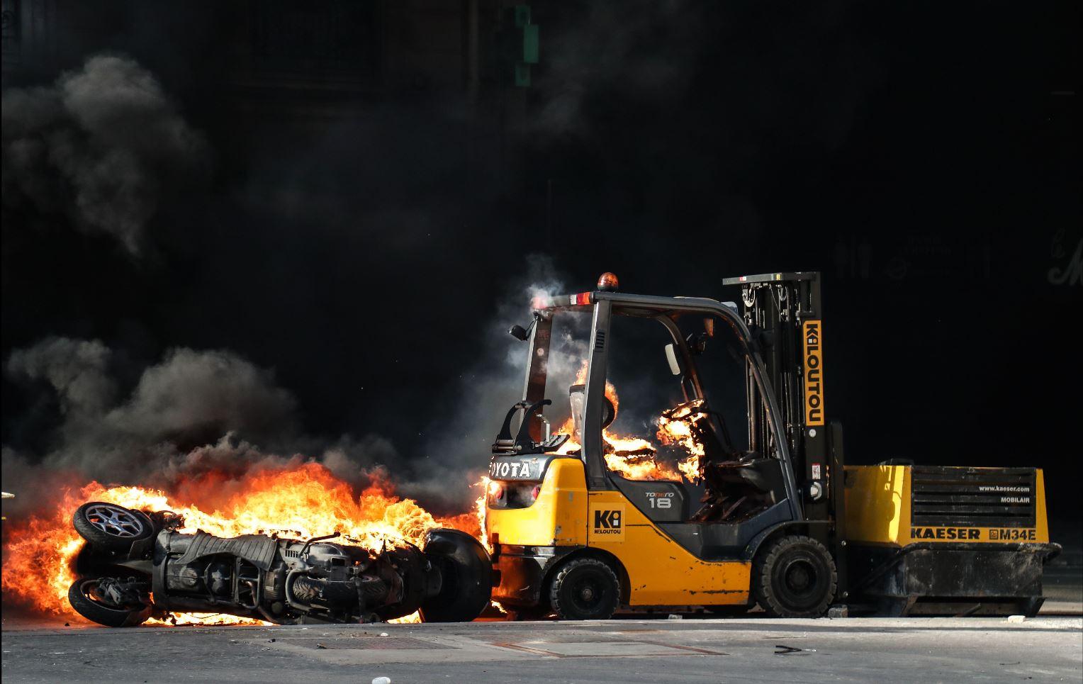 Una motocicleta y una carretilla elevadora incendiadas se muestran en la avenida Champs-Elysees en París, este 16 de marzo de 2019, durante  enfrentamientos entre las fuerzas de la policía antidisturbios y los manifestantes del chaleco amarillo. (Foto: AFP)