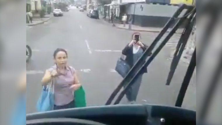 Dos mujeres se paran a media calle en su intento de que el piloto del Express Naranjo les abra la puerta del bus. (Captura de pantalla)