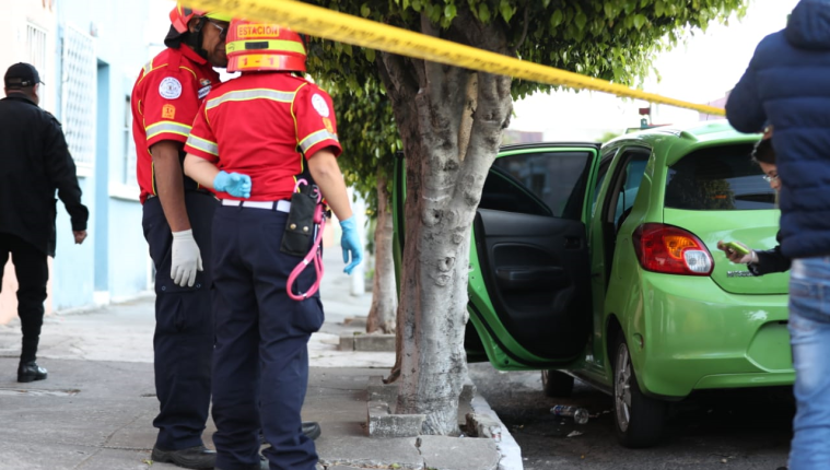 Socorristas observan las pastillas que se localizaron en el exterior del vehículo donde fue hallada la víctima. (Foto Prensa Libre: Óscar Rivas)