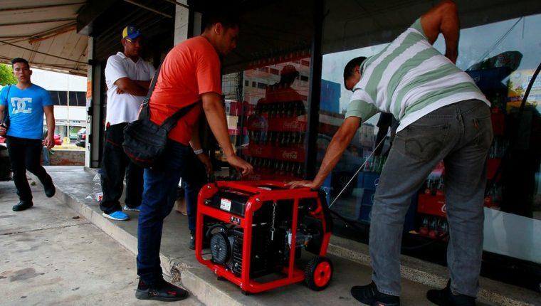 Dos hombre tratan de encender un generador frente a un supermercado de Maracaibo.