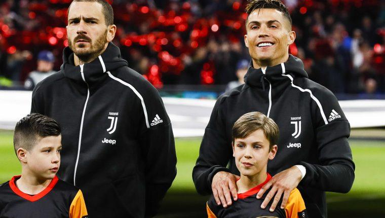 Cristiano Ronaldo (d) y Leonardo Bonucci (i) de la Juventus escuchan el himno este miércoles, durante el partido de ida de cuartos de final de la Liga de Campeones UEFA, entre el Ajax Amsterdam y la Juventus FC, en Ámsterdam (Holanda). (Foto Prensa Libre: EFE)