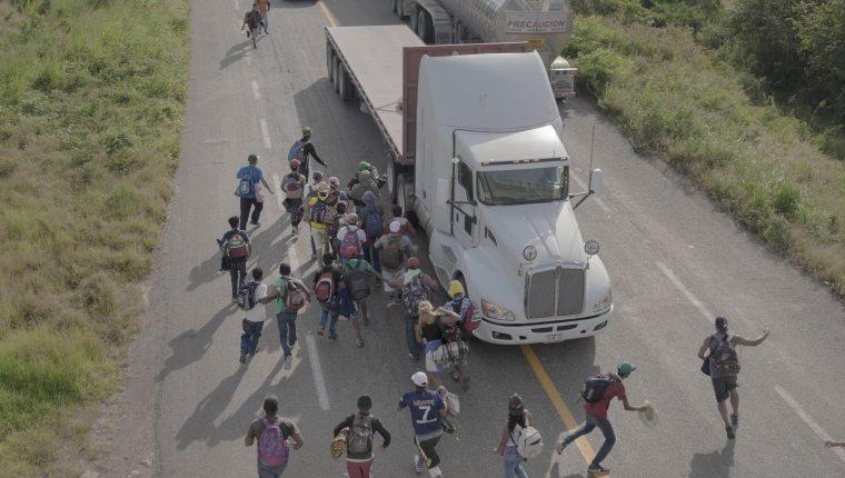 """Migrantes corren hacia un camión para pedirles """"jalón"""" en una carretera de Tapanatepec, México. (Foto Prensa Libre: EFE)"""