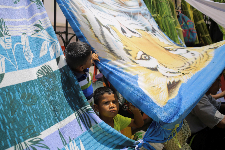 AME385. TEGUCIGALPA (HONDURAS), 13/04/2019.- Dos niños juegan mientras sus padres venden ramos de palma para el tradicional Domingo de Ramos de la Semana Santa este sábado, en la Plaza Central de Tegucigalpa (Honduras). EFE/Gustavo Amador