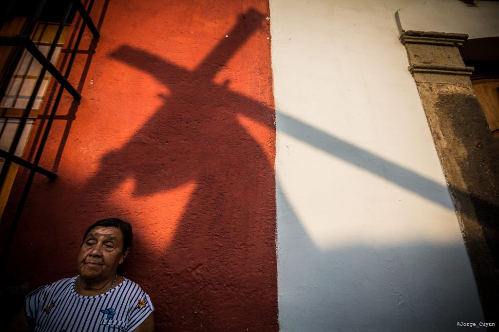 Una mujer observa el paso del nazareno en las calles previas al parque central de la ciudad colonial. Foto Prensa Libre: Jorge Cuyun