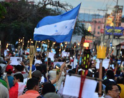 Alrededor de 5 mil hondureños salieron con antorchas para exigir la salida del presidente Juan Orando Hernández. (Foto Prensa Libre: AFP)