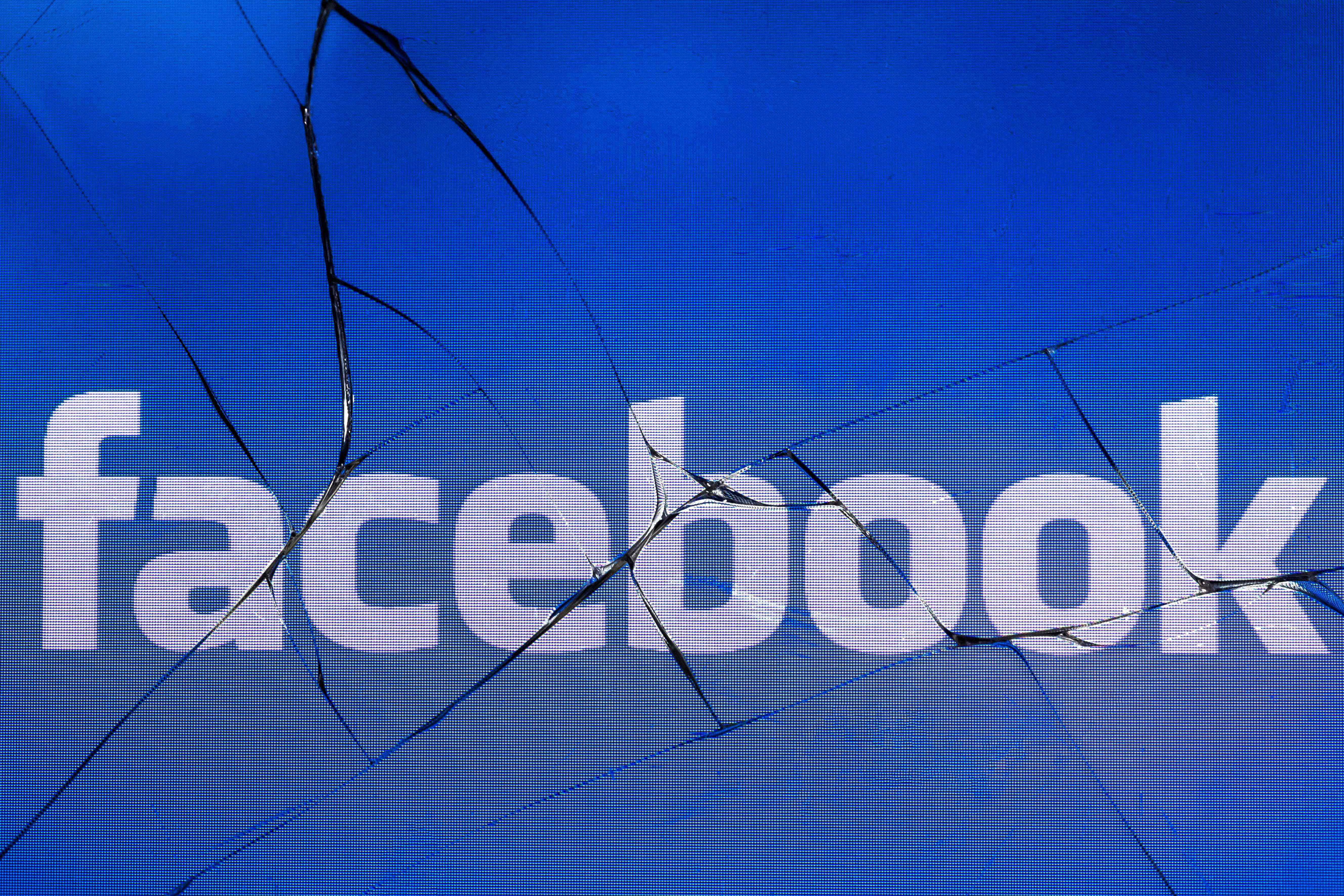 "(FILES) In this file photo taken in Paris on May 16, 2018 shows the logo of the social network Facebook on a broken screen of a mobile phone. - Facebook on April 10, 2019 ramped up its battle against misinformation, taking aim at groups spreading lies and adding ""trust"" indicators to news feeds. Moves outlined by Facebook vice president of integrity Guy Rosen were described as part of a strategy launched three years ago to ""remove, reduce and inform"" when it comes for troublesome content posted at the leading social network's family of services. (Photo by JOEL SAGET / AFP)"