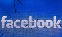 """(FILES) In this file photo taken in Paris on May 16, 2018 shows the logo of the social network Facebook on a broken screen of a mobile phone. - Facebook on April 10, 2019 ramped up its battle against misinformation, taking aim at groups spreading lies and adding """"trust"""" indicators to news feeds. Moves outlined by Facebook vice president of integrity Guy Rosen were described as part of a strategy launched three years ago to """"remove, reduce and inform"""" when it comes for troublesome content posted at the leading social network's family of services. (Photo by JOEL SAGET / AFP)"""