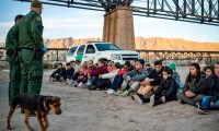 "(FILES) In this file photo taken on March 20, 2019 a group of about 30 Brazilian migrants, who had just crossed the border, sit on the ground near US Border Patrol agents, on the property of Jeff Allen, who used to run a brick factory near Mt. Christo Rey on the US-Mexico border in Sunland Park, New Mexico. - The White House confirmed on April 14, 2019 it is looking at ways to transfer undocumented migrants to US sanctuary cities as Democrats accused President Donald Trump of creating ""manufactured chaos"" at the US-Mexico border.""This is an option on the table,"" White House press secretary Sarah Sanders said in an interview on ABC's ""This Week.""Trump ""heard the idea, he likes it, so –- well, we're looking to see if there are options that make it possible and doing a full and thorough and extensive review,"" she said. (Photo by Paul Ratje / AFP)"