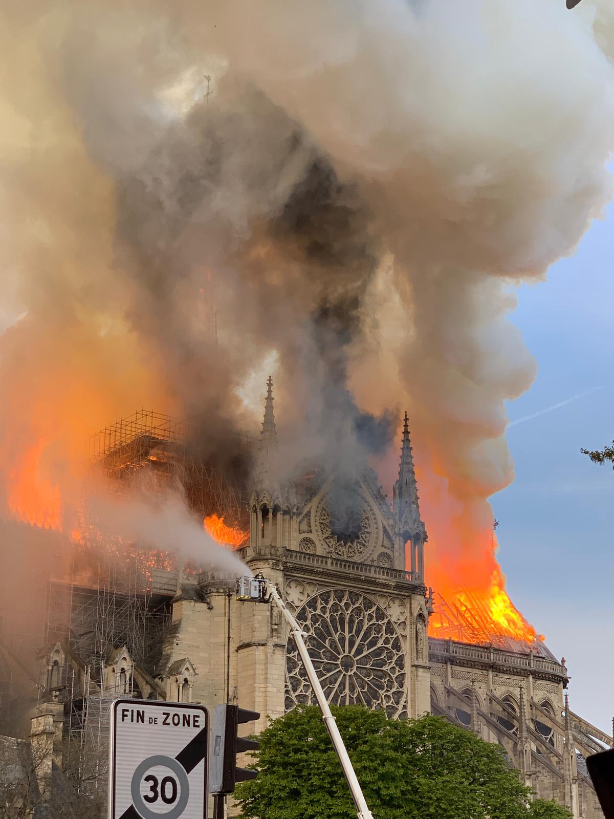 Flames and smoke are seen billowing from the roof at Notre-Dame Cathedral in Paris on April 15, 2019. - A fire broke out at the landmark Notre-Dame Cathedral in central Paris, potentially involving renovation works being carried out at the site, the fire service said.Images posted on social media showed flames and huge clouds of smoke billowing above the roof of the gothic cathedral, the most visited historic monument in Europe. (Photo by Patrick ANIDJAR / AFP)