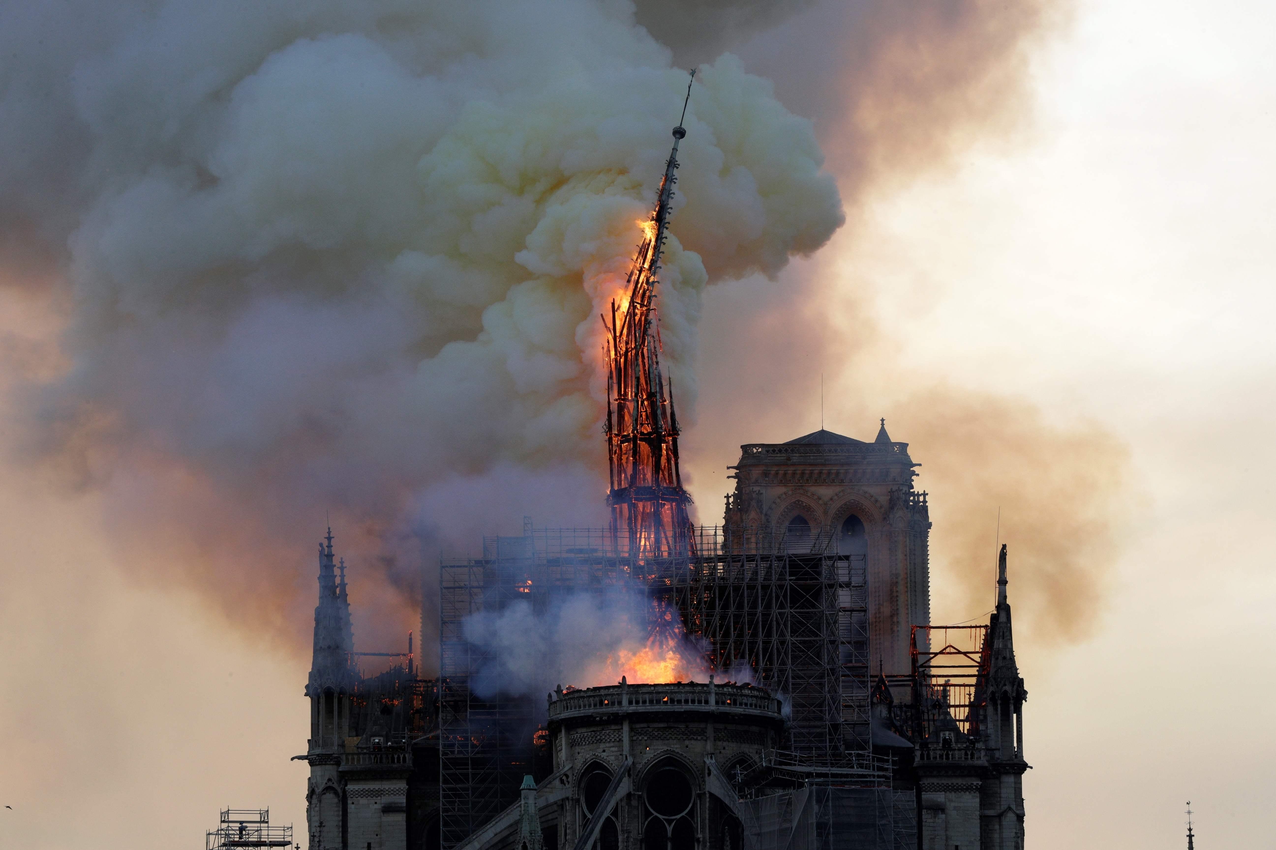 Momento en que se derrumba la aguja de la emblemática catedral de Notre-Dame, en París. (Foto Prensa Libre: AFP)