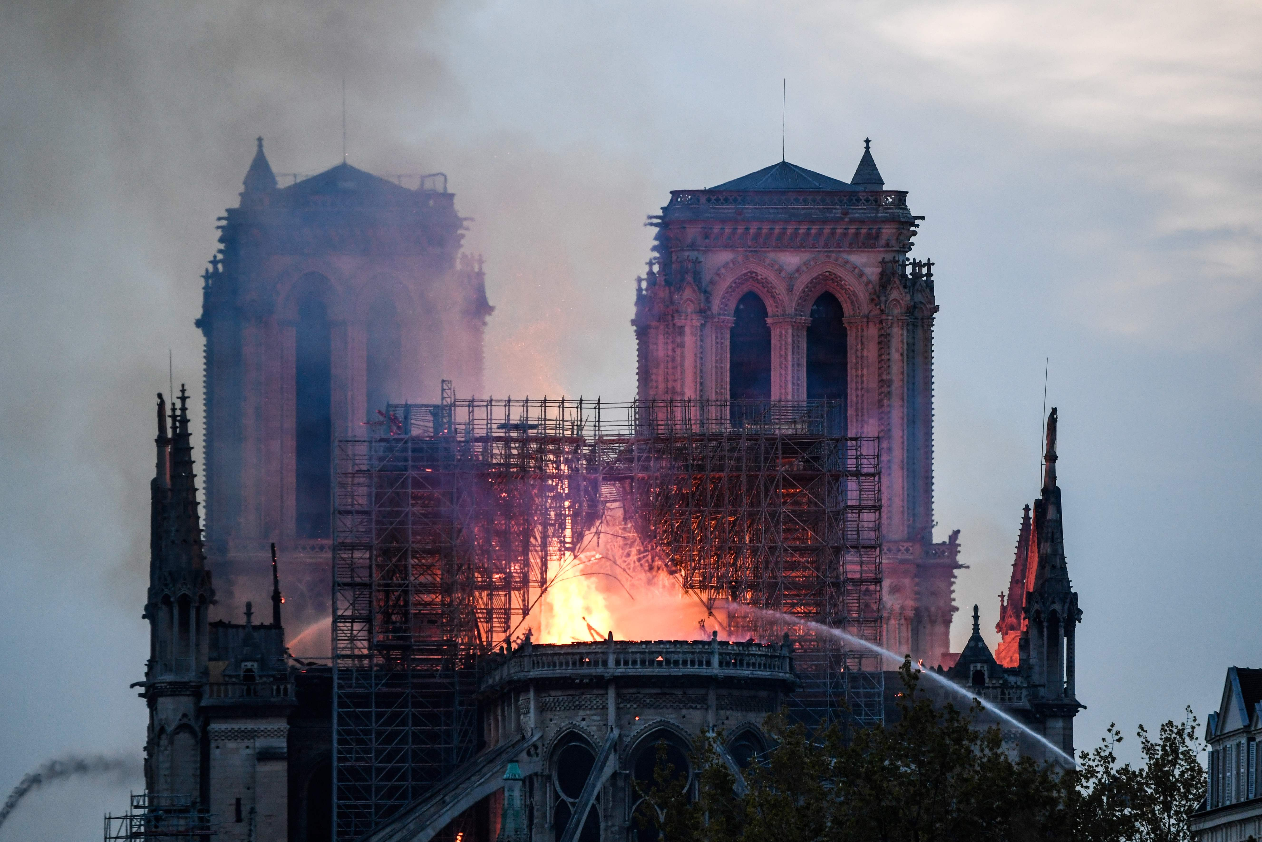 Firefighters douse flames and smoke billowing from the roof at Notre-Dame Cathedral in Paris on April 15, 2019. - A fire broke out at the landmark Notre-Dame Cathedral in central Paris, potentially involving renovation works being carried out at the site, the fire service said. (Photo by Bertrand GUAY / AFP)