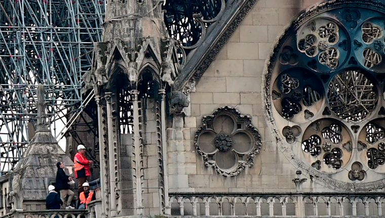 Inspectors are seen on the roof of the landmark Notre-Dame Cathedral in central Paris on April 16, 2019, the day after a fire ripped through its main roof. - A major fire broke out at the landmark Notre-Dame Cathedral in central Paris sending flames and huge clouds of grey smoke billowing into the sky, the fire service said. The flames and smoke plumed from the spire and roof of the gothic cathedral, visited by millions of people a year, where renovations are currently underway. (Photo by Lionel BONAVENTURE / AFP)