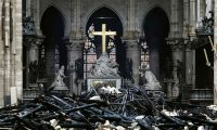 A picture taken on April 16, 2019 shows the altar surrounded by charred debris inside the Notre-Dame Cathedral in Paris in the aftermath of a fire that devastated the cathedral. - French investigators probing the devastating blaze at Notre-Dame Cathedral on April 15, 2019, questioned workers who were renovating the monument on April 16, as hundreds of millions of euros were pledged to restore the historic masterpiece. As firefighters put out the last smouldering embers, a host of French billionaires and companies stepped forward with offers of cash worth around 600 million euros ($680 million) to remake the iconic structure. (Photo by LUDOVIC MARIN / AFP)