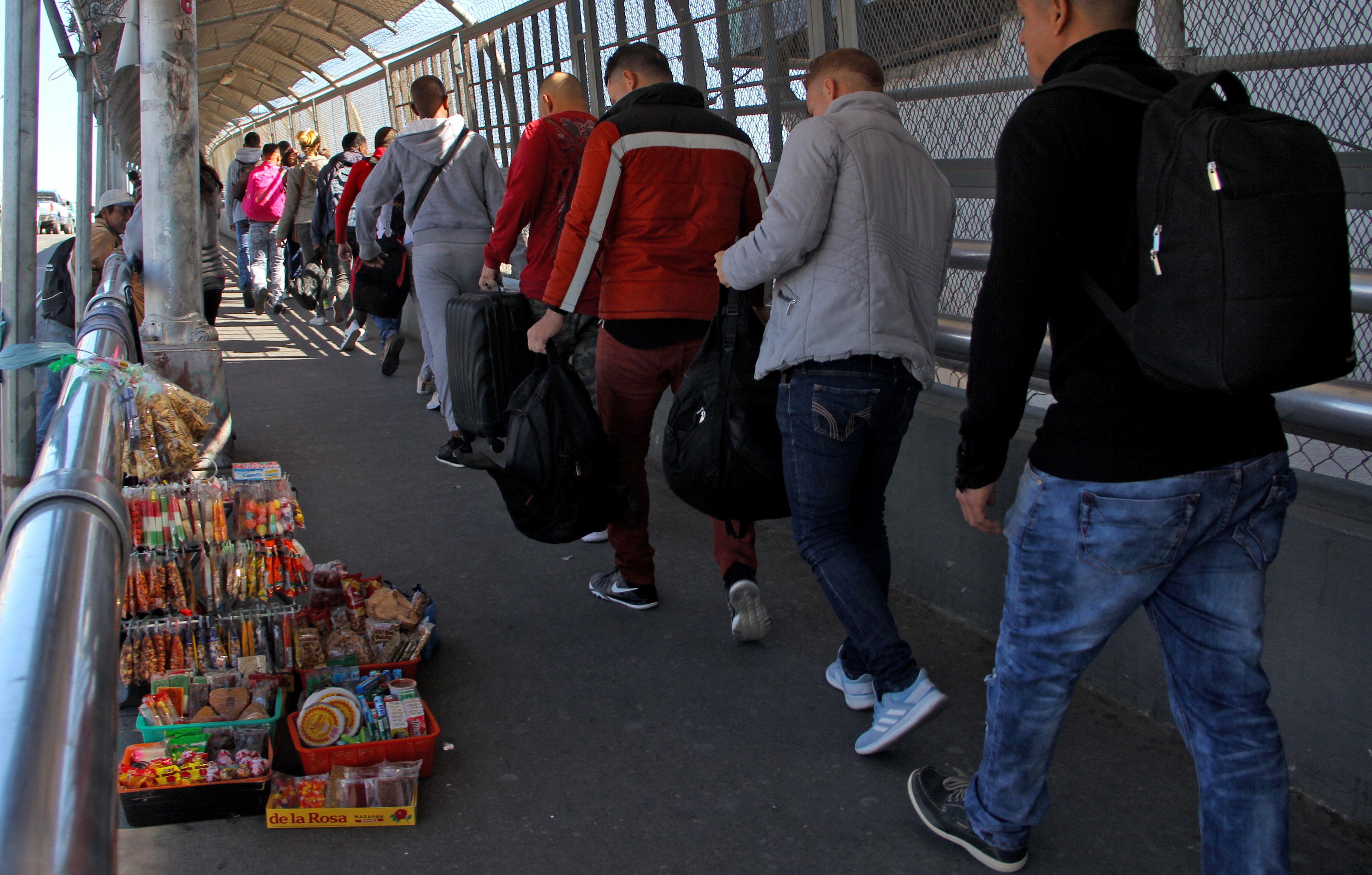 Solicitantes de asilo cruzan el paso fronterizo entre Tijuana y San Diego. (Foto Prensa Libre: AFP)