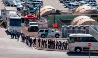 Migrants board buses to take them to shelters after being released from migration detention as construction of a new migrant processing facility is underway at the Customs and Border Protection - El Paso Border Patrol Station on the east side of El Paso on April 28, 2019. - Migrants kept behind concertina and barbed wire underneath the the Paso Del Norte International Bridge in downtown El Paso were moved to temporary tents here after major outcry against the practice. (Photo by Paul RATJE / AFP)