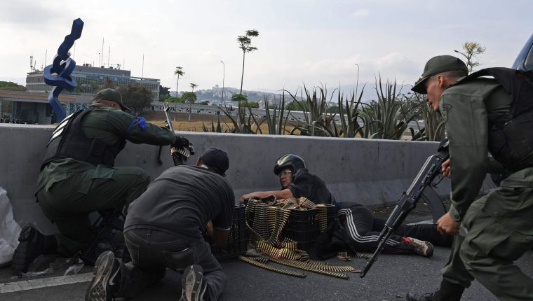 Los soldados leales al líder opositor venezolano y al autoproclamado presidente Juan Guaido toman posición frente a la base de La Carlota en Caracas. Foto Prensa Libre: EFE