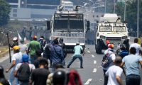 "Opposition demonstrators clash with soldiers loyal to Venezuelan President Nicolas Maduro after troops joined opposition leader Juan Guaido in his campaign to oust Maduro's government, in the surroundings of La Carlota military base in Caracas on April 30, 2019. - Guaido -- accused by the government of attempting a coup Tuesday -- said there was ""no turning back"" in his attempt to oust President Nicolas Maduro from power. (Photo by Federico PARRA / AFP)"