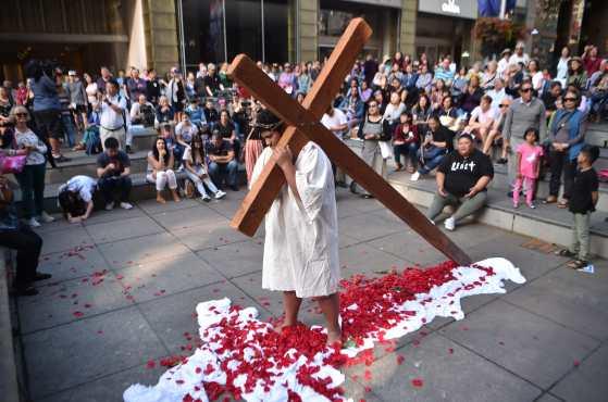 Un miembro de la iglesia sostiene una cruz durante una recreación de la Biblia, la crucifixión de Jesucristo el Viernes Santo, en Sydney, Australia. Foto Prensa Libre: AFP
