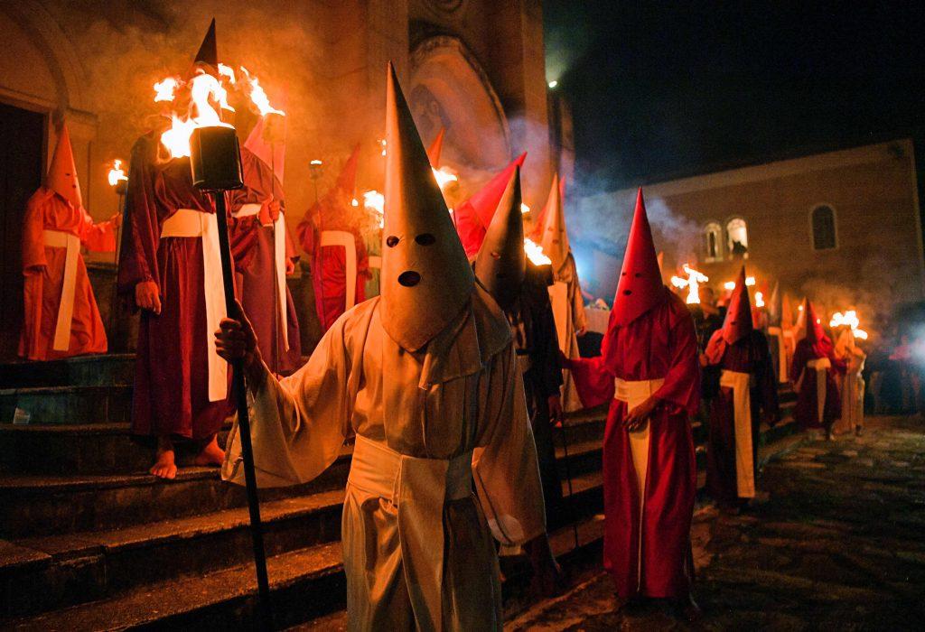 """Fieles católicos encapuchados que representan a los soldados romanos, conocidos como """"Farricocos"""", llevan antorchas encendidas durante la procesión anual de la Semana Santa de Fogareu en Goias, 350 km al oeste de Brasilia, Brasil. Foto Prensa Libre: AFP"""