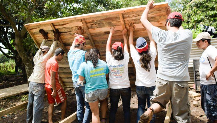 Voluntarios y familia beneficiada construyen una de las viviendas en comunidad beneficiada anteriormente. (Foto Prensa Libre: Cortesía Techo Guatemala).