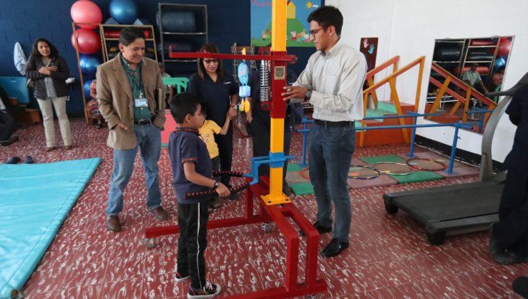 Universitario ayuda a uno de los pacientes de Fundabiem a utilizar la maquina que donó. (Foto Prensa Libre: María Longo)