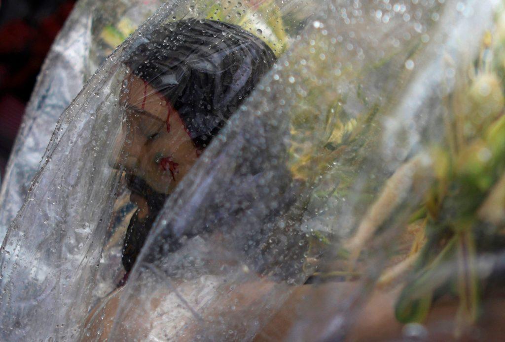 En El Salvador las imágenes fueron cubiertas con plástico debido a la lluvia. Foto Prensa Libre: AFP