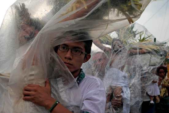 """Salvadoreños llevan consigo imágenes de Jesús durante """"La Procesión de los Cristos"""" en Izalco, El Salvador. Foto Prensa Libre: AFP"""
