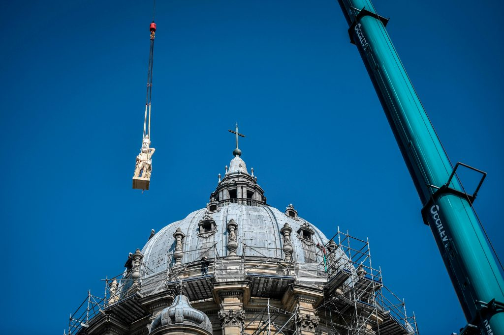 Una grúa levanta una de las esculturas de genios y ángeles restauradas durante su reinstalación en la cúpula de la iglesia de Notre Dame. Foto Prensa Libre: AFP