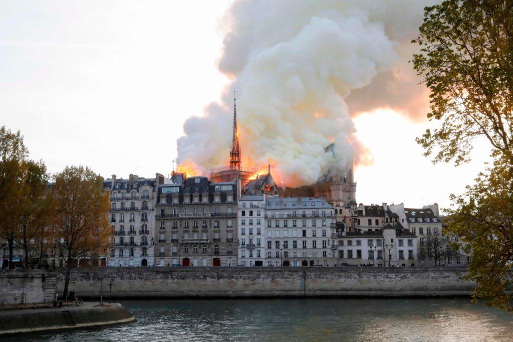 Humo y llamas salen desde la catedral de Notre-Dame, vista desde el río Sena. (Foto Prensa Libre: AFP)