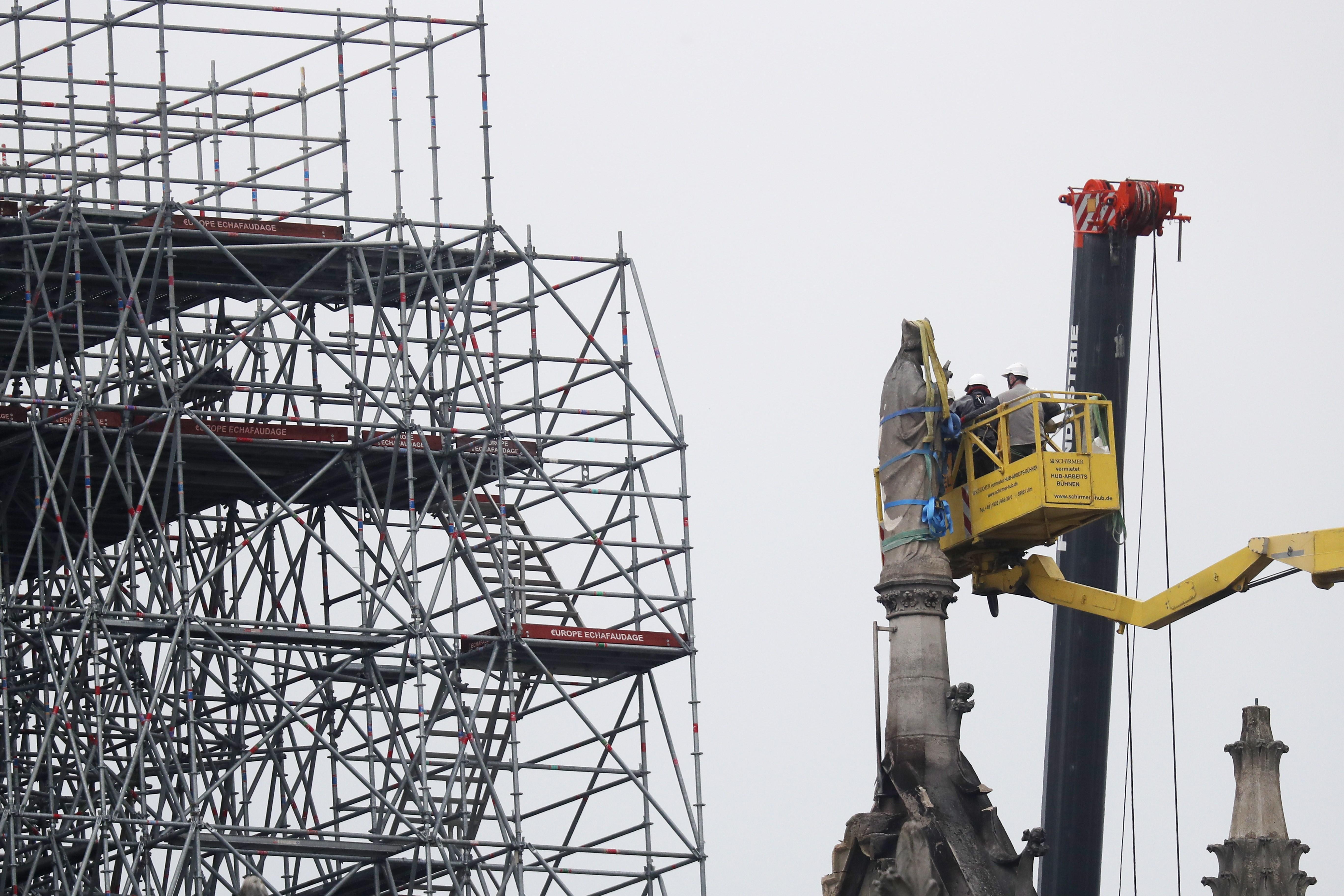 Personas protegen una de las estatuas para que no se deteriore más después del incendio. Foto Prensa Libre: EFE