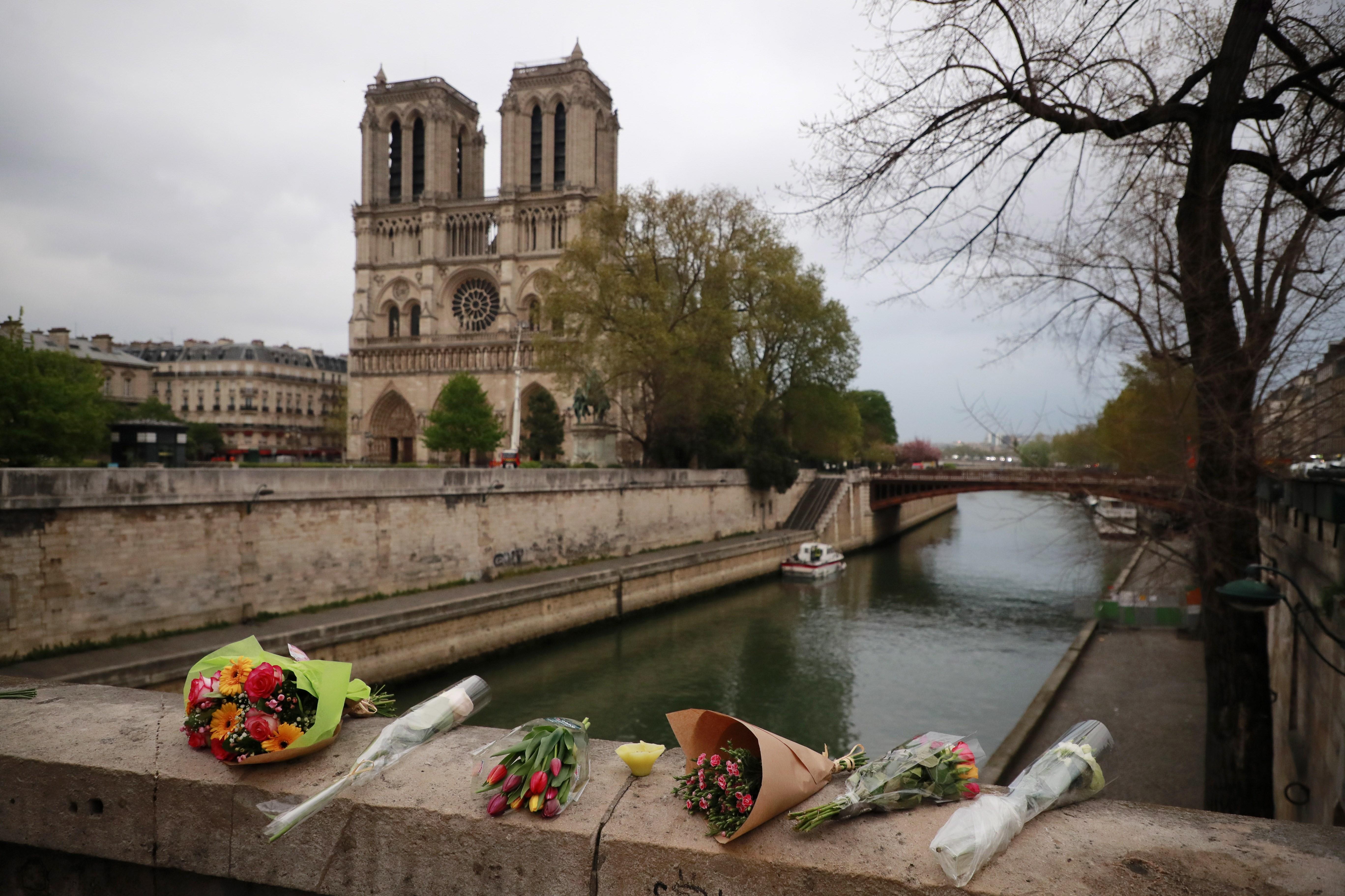 Arreglos florales han dejado los visitantes en los alrededores de la Catedral de Notre Dame. Foto Prensa Libre: AFP