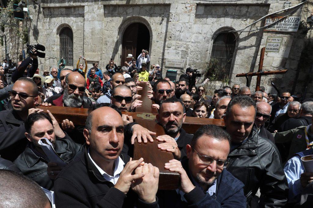 Los miembros de la parroquia católica palestina local llevan una cruz de madera a lo largo de la Vía Dolorosa (Camino del sufrimiento) en la Ciudad Vieja de Jerusalén durante la procesión del Viernes Santo. Foto Prensa Libre: AFP
