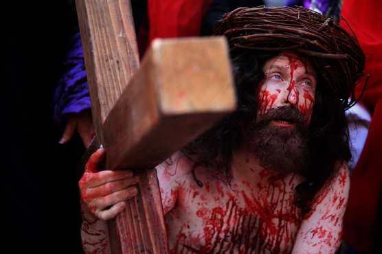Un peregrino católico lleva una cruz a lo largo de la Vía Dolorosa (Camino del sufrimiento) mientras recrea la pasión de Jesucristo en la Ciudad Vieja de Jerusalén. Foto Prensa Libre: AFP