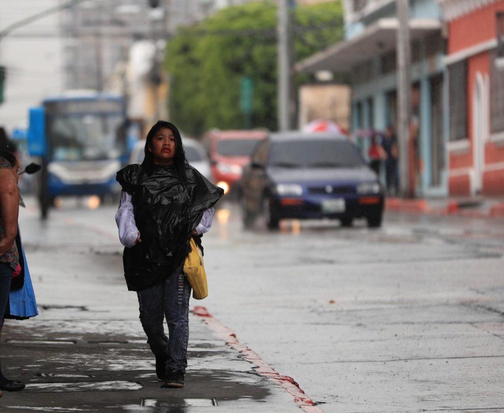 Algunas personas improvisaron sus trajes ante la sorpresiva lluvia. Foto Prensa Libre: Carlos Hernández