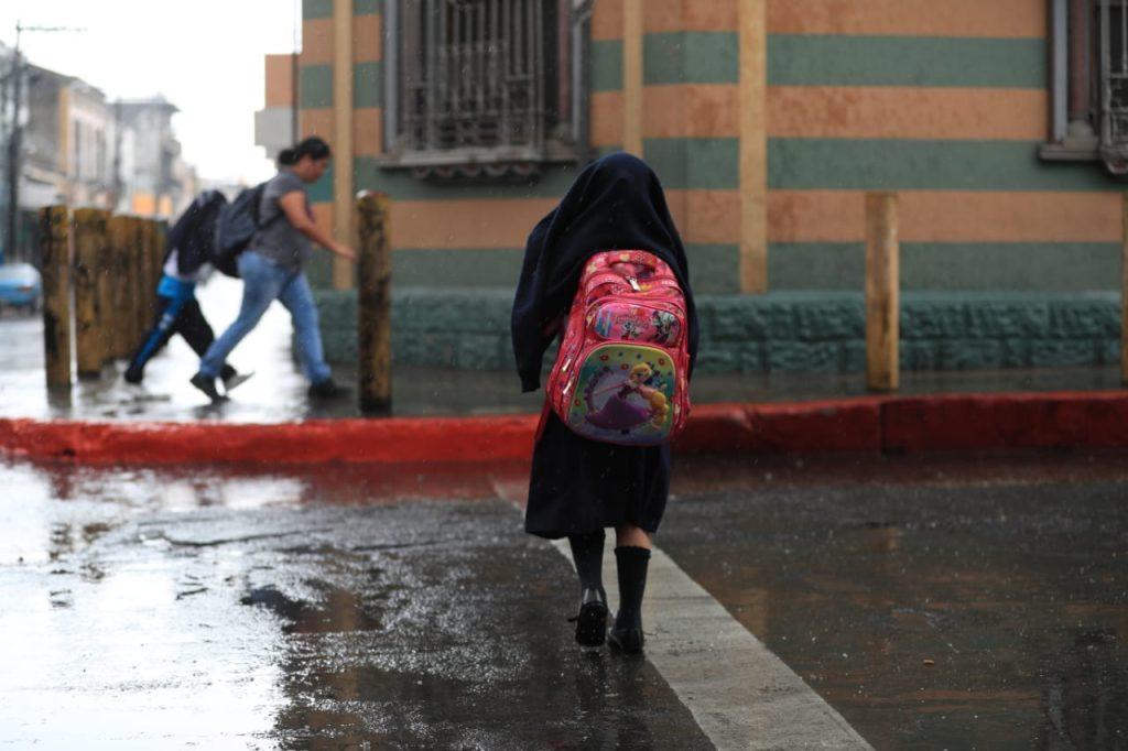 Jóvenes estudiantes se mojaron al salir de sus clases este medio día. Foto Prensa Libre: Carlos  Hernández