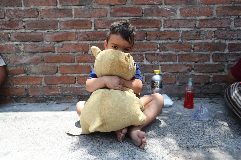 Un niño abraza su perrito de peluche.